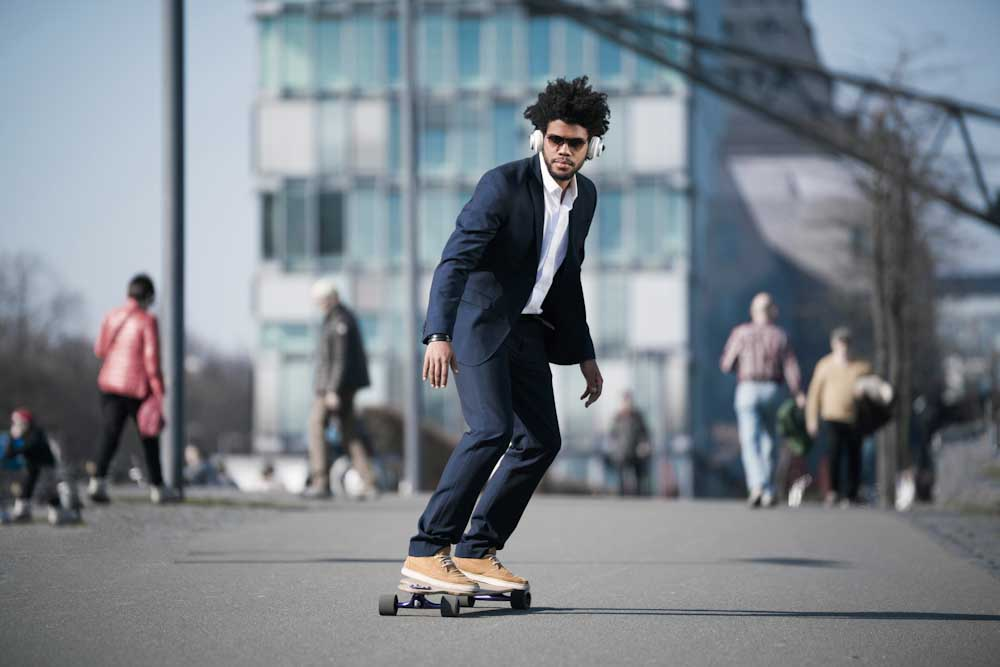 Man in suit riding skateboard